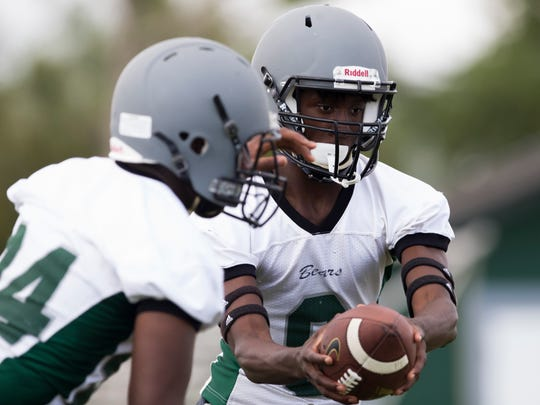 Transfer from Lely High School Jacquez Carter, right, takes some of his first snaps as quarterback for Palmetto Ridge High School during their first spring practice Monday, April 24, 2017 in Naples.