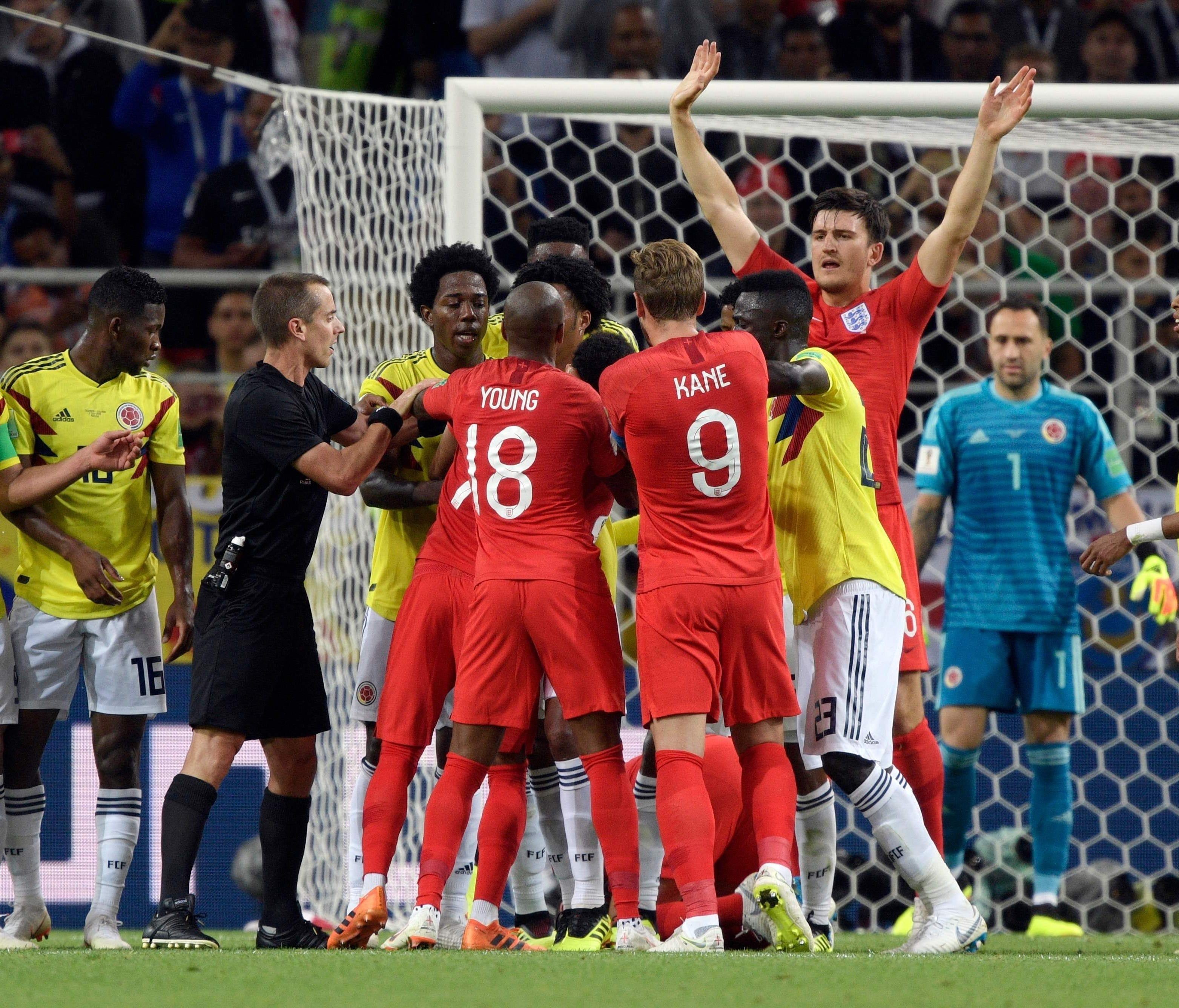 English and Colombian players quarrel as U.S. referee Mark Geiger tries to mediate during their World Cup match.