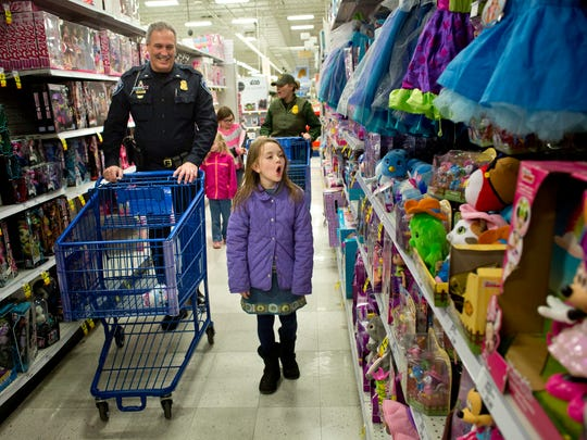 Olivia Fowler, 8, of Avoca, reacts as she sees toys while walking with Port Huron Police Lt. Scott Pike during Shop with a Cop Tuesday, Dec. 15, 2015 at Meijer in Fort Gratiot.