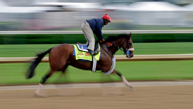Exercise rider Kelvin Pahal takes Kentucky Derby hopeful Wicked Strong for a morning workout at Churchill Downs April 29.