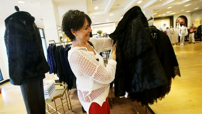 Linda Marie looks at one of the coats from the fall line as she stopped in to shop during her lunch break at Chico's in Bell Tower Shops.