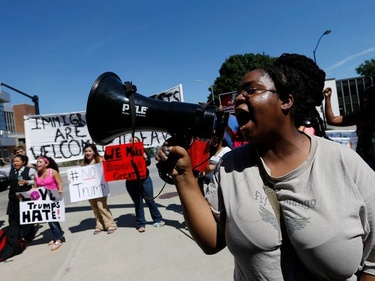 Student activist Kaija Carter leads a group of protesters in a chant Friday, Aug. 5, 2016, outside of a rally for Republican presidential nominee Donald Trump at Hy-Vee Hall in downtown Des Moines.