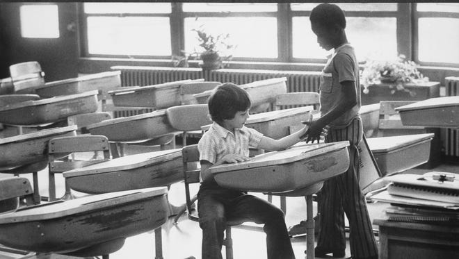 At Greenwood Elementary, Mark Stewart, 8, seated, exchanged introductions with a new classmate, Darrel Hughes, also 8. Photo by Michael Coers Sept. 3, 1975 Published in the Louisville Times on 9/4/1975