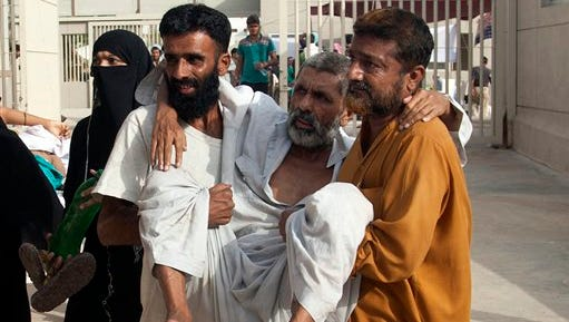 Pakistani family members bring an elderly person suffering from a heatstroke to a hospital in Karachi, Pakistan, Saturday, June 27, 2015. A Pakistani official says the devastating weeklong heat wave in the southern port city of Karachi has killed over 1,200 people despite a respite in temperatures. (AP Photo/Shakil Adil)