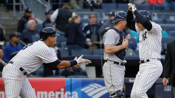 New York Yankees' Mark Teixeira, right, is greeted by Alex Rodriguez at the plate after hitting a three-run home run against the Houston Astros during the seventh inning of a baseball game, Thursday, April 7, 2016, in New York. (AP Photo/Julie Jacobson)