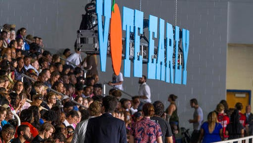 Supporters look for seats under a vote early sign at the University of North Florida Arena in Jacksonville, Fla., Thursday, Nov. 3, 2016, as they wait for President Barrack Obama to speak at a campaign rally for Democratic presidential candidate, Hillary Clinton.
