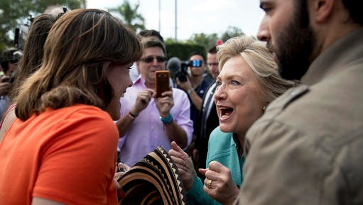 Democratic presidential candidate Hillary Clinton, center, accompanied by actor Jencarlos Canela, right, greets people outside an early voting center in West Miami, Fla., Saturday, Nov. 5, 2016.