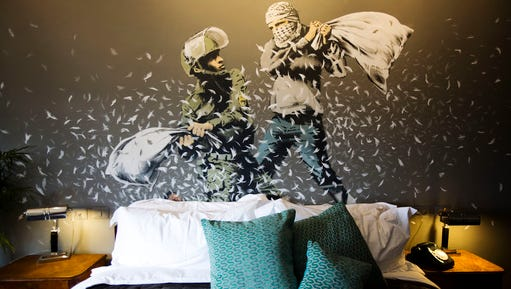 """A Banksy wall painting showing Israeli border policeman and Palestinian in a pillow fight is seen in one of the rooms of the """"The Walled Off Hotel"""" in the West Bank city of Bethlehem, Friday, March 3, 2017. The owner of a guest house packed with the elusive artist Banksy's work has opened the doors of his West Bank establishments to media, showcasing its unique """"worst view in the world."""" The nine-room hotel named """"The Walled Off Hotel"""" will officially open on March 11."""