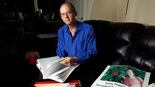 """FILE - In this Oct. 4, 2016, file photo, Jeff Gillis looks through documents he has collected in support of his wife in Houston. The husband of U.S. citizen Phan """"Sandy"""" Phan-Gillis, who has been charged in China with spying, has spent months trying to prove his wife's innocence with the little information he had. A Chinese court on Tuesday, April 25, 2017, sentenced Phan-Gillis to 3 ½ years in prison for spying charges, in a case that has drawn criticism from the United Nations and human rights advocates."""