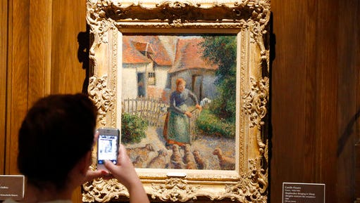 "FILE - In this Feb. 8, 2014, file photo, a visitor to the Fred Jones Jr. Museum of Art at the University of Oklahoma in Norman, Okla., takes a photograph of a piece called ""Shepherdess Bringing in Sheep"" by French impressionist artist Camille Pissarro, at the museum. The 1886 painting that was stolen as part of a Nazi looting campaign that stretched across Europe during World War II has transferred from the University of Oklahoma to Paris and will be on display at the French museum, Musee d'Orsay, for five years before returning to the university in alternating three-year intervals."