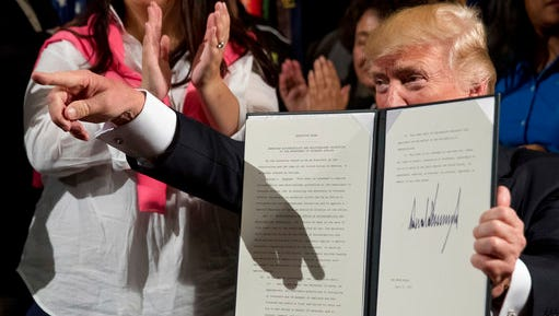 """President Donald Trump holds up an Executive Order on """"Improving Accountability and Whistleblower Protection"""" after signing it at the Department of Veterans Affairs, Thursday, April 27, 2017, in Washington."""