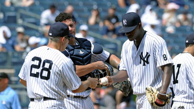 New York Yankees pitcher Luis Severino, right, hands the ball to manager Joe Girardi (28) as catcher Gary Snchez looks on during the fourth inning of a baseball game against the Tampa Bay Rays, Sunday, Aug.14, 2016, at Yankee Stadium in New York.