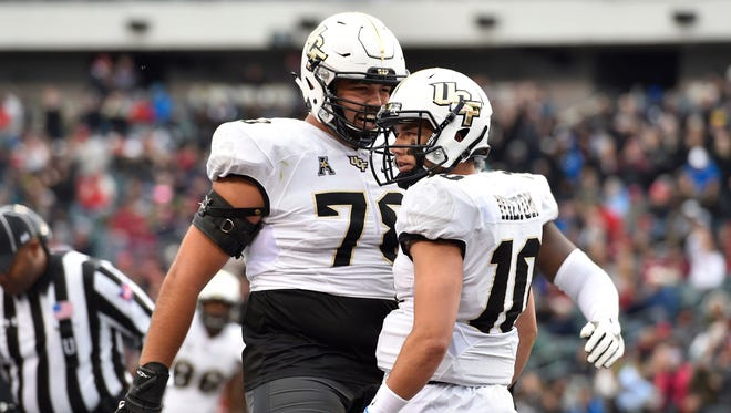 UCF Knights quarterback McKenzie Milton (10), right, celebrates in the end zone with offensive lineman Wyatt Miller.