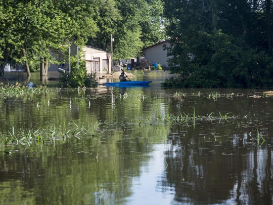 A kayaker makes their way through floodwaters down