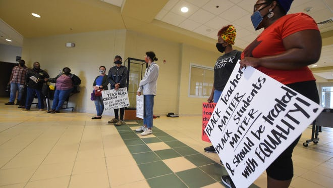 People protest prior to the Pender County Board of Education meeting at Topsail High School Tuesday. The Pender County NAACP organized a protest after the school hired outside counsel over alleged racial slurs by school staff.