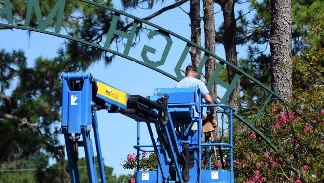 Crews with New Hanover County take down the sign at the entrance of Hugh MacRae in Wilmington on Tuesday, July 14. The New Hanover Board of Commissioners voted Monday to change the name of county-owned Hugh MacRae Park to Long Leaf Park.