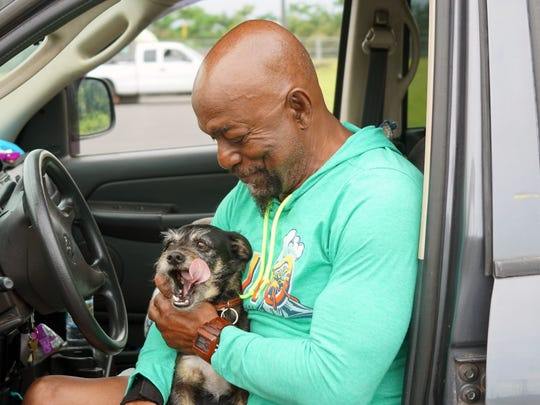 Big Island evacuee Sammy Walton pets his dog, Sugar, while sitting in his truck outside a Red Cross shelter in Pahoa, Hawaii, on May 5, 2018.