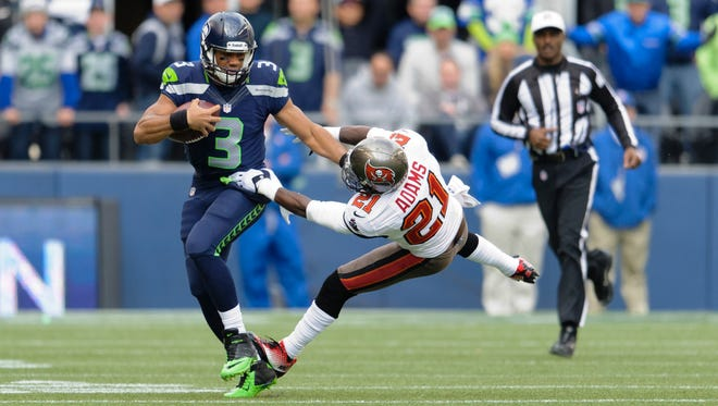 Seattle Seahawks quarterback Russell Wilson (3) stiff arms Tampa Bay Buccaneers defensive back Michael Adams (21) during the 1st half at CenturyLink Field.