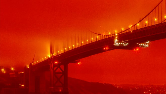 In this photo provided by Frederic Larson, the Golden Gate Bridge is seen at 11 a.m. PT, Wednesday, Sept. 9, 2020, in San Francisco, amid a smoky, orange hue caused by the ongoing wildfires.