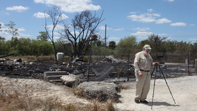 Monroe Station fire aftermath: Clyde Butcher prepares  to pack up  his camera  after taking photos of the aftermath of a fire on Sunday that destroyed Monroe Station in Ochopee. Monroe Station was on the  U.S. National Register of Historic Places and was originally constructed in the 1920s.  The cause of  the fire, which happened late Saturday night, is currently under investigation. .