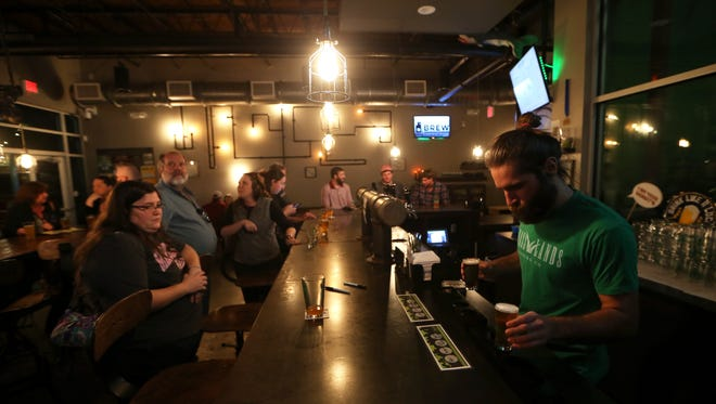 Bartender Andrew Pitts sets out a tasting flight of in-house brews at Grasslands Brewery Wednesday, Nov. 23, 2016. Tasting rooms like this one make up a large part of the local brewery's revenue and allow them to grow into distribution.