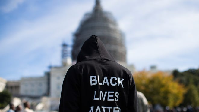 "FILE - In this Oct. 10, 2015 file photo, a man wears a hoodie which reads, ""Black Lives Matter"" as stands on the lawn of the Capitol building on Capitol Hill in Washington during a rally to mark the 20th anniversary of the Million Man March. Fifty years ago, Martin Luther King Jr. asked Americans, ""Where do we go from here?"" His warning of chaos or community squarely confronted racism, and marked a shift from his emphasis on nonviolence to a demand for full economic and political equality. Younger generations of black activists say they prefer the pointed, more forceful King to the Nobel Peace Prize-winning pacifist who preached love over hate. (AP Photo/Evan Vucci, File)"