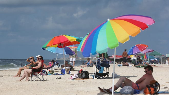 Beachgoers at St. George Island take cover under umbrellas. Before heading out in the sun, apply screen, wear hats and protective clothing.