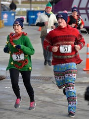 Adorned in their holiday ugly sweater best, finishers in the first 104.7 KCLD Ugly Sweater-A-Thon 5K cross the finish line Saturday morning at St. Cloud State University.