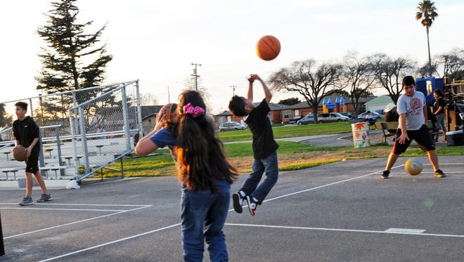 In the fading light, kids enjoy playing basketball at Closter Park in east Salinas.