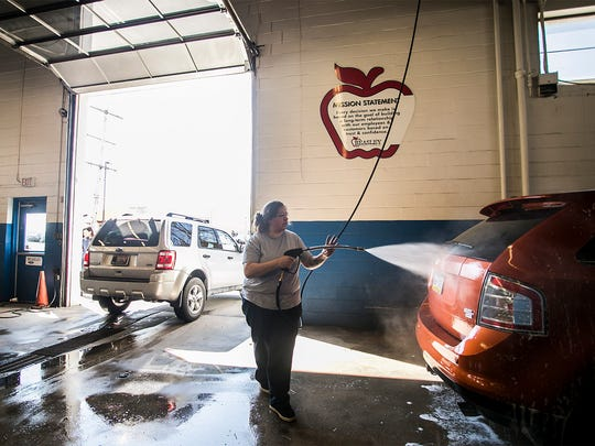 Beasley Ford Lincoln car detailer Lori Taylor, washes a 2007 Ford Edge Tuesday, March, 8, 2016, in Springettsbury Twp. Dealerships in York and nationwide have reported a small increase in new car leases and consumers trending toward larger vehicles, including SUVs and trucks. Amanda J. Cain photo