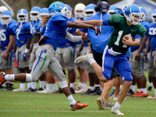 University of West Florida's Quarter back Gunnar Ballant grabs the shirt of Asante Griffin  Saturday during the teams first intrasquad scrimmage at UWF.