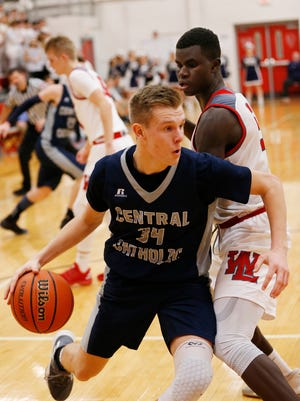 Carson Barrett of Central Catholic works around Nelson Mbongo of West Lafayette along the baseline Friday, February 9, 2018, at West Lafayette. West Lafayette defeated CC 56-53.