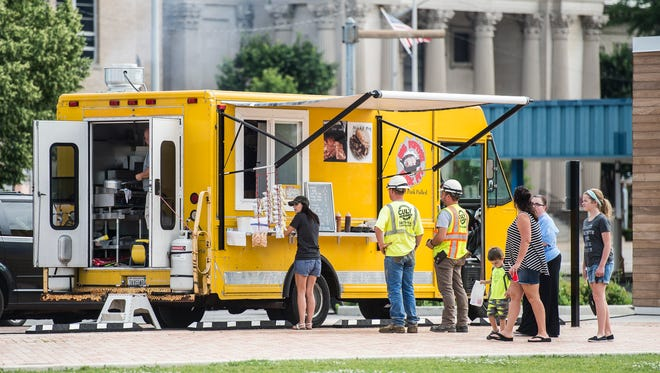 Locals enjoy lunch from area food trucks at Elstro Plaza in downtown Richmond on June 20, 2018.