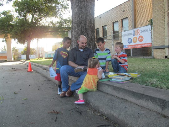 North Texas Area United Way CEO Matt Yell reads stories to children during the Fatherhood Fall Festival sponsored by the United Way's Dad's Workshop. Programs focusing on helping families took a bold step forward in 2016 in Wichita Falls.