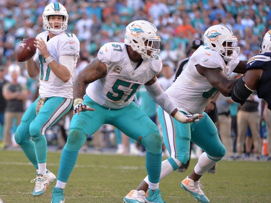 Miami Dolphins quarterback Ryan Tannehill (17) looks to pass while protected by center Mike Pouncey (51) and offensive guard Laremy Tunsil (67) during the second half against the San Diego Chargers at Qualcomm Stadium. Miami won 31-24.