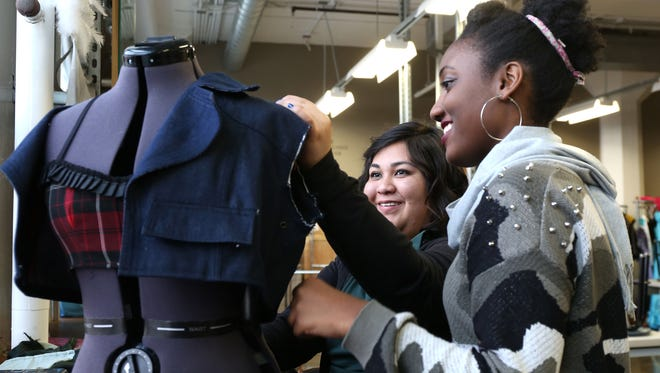 Genesis Galdamez, a senior from Des Moines North High School, left, and Meccah Muhammad, a senior from Roosevelt High School, work on a clothing project during fashion design class on Dec. 18 at Central Campus in Des Moines.