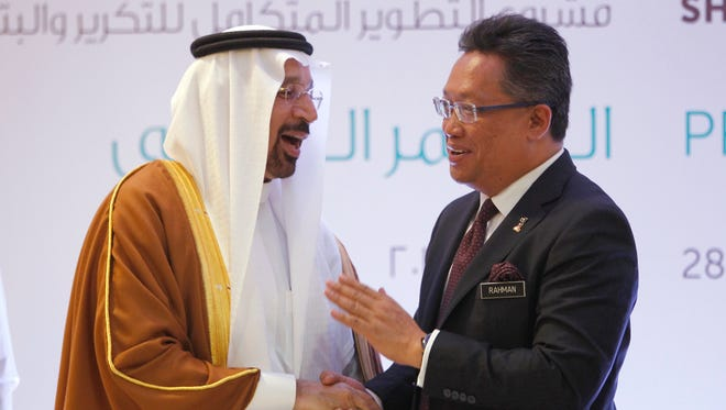 Saudi's Energy Minister Khalid Al-Falih, left, shakes hands with Malaysia's Minister in the Prime Minister's Department Abdul Rahman Dahlan during a press conference at a hotel in Kuala Lumpur, Malaysia, Tuesday, Feb. 28, 2017.