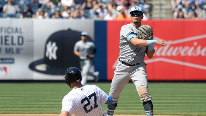 New York Yankees' Giancarlo Stanton (27) is out at second base as Tampa Bay Rays shortstop Willy Adames relays the ball to first while attempting to complete the double play during the fourth inning of a baseball game Sunday, June 17, 2018, at Yankee Stadium in New York.