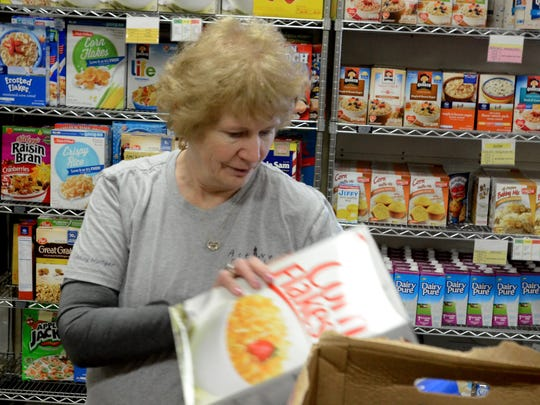 Active Faith volunteer Judy Kushiner prepares to stock the shelves of the South Lyon food pantry on Monday.