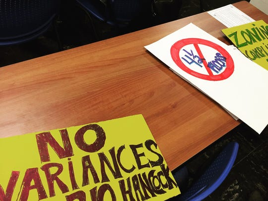 Signs made by attendees of Ithaca's Board of Zoning of Appeals meeting against variances for a housing project at 210 Hancock St.