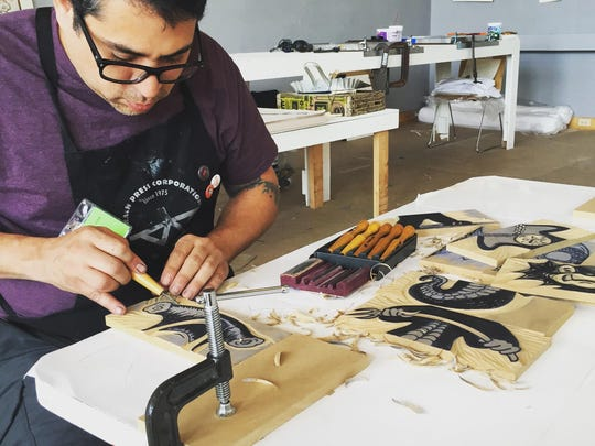 Artist-in-residence Joseph Velasquez hand carves blocks that will be used to print prizes to be awarded at the Carnival of Ink during the Midsummer Festival of the Arts this weekend at the John Michael Kohler Arts Center.