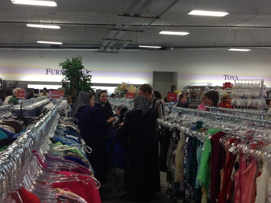 Shoppers at the Goodwill store look through clothing racks.