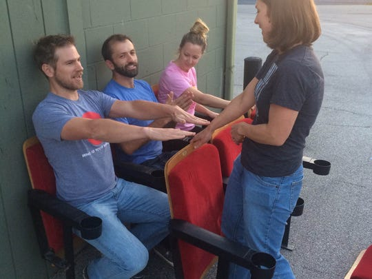 """Tommy Haines, from left, Andrew Sherburne, Emily Salmonson and Laura Bergus of FilmScene test out seating for this weekend's """"tiny tent cinema."""" FilmScene will show the documentary """"Tiny: a Story About Small Living"""" this weekend on the pedestrian mall."""