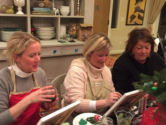 From left, Katie Reding Pickels, Stacey Sutter and Sarah Canzano work side-by-side at a painting party.