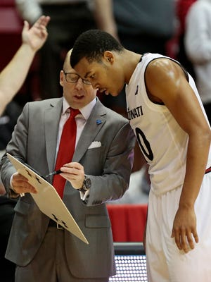 Cincinnati Bearcats head coach Mick Cronin and guard Troy Caupain (10) set up a play in the second half of the NCAA basketball game between the Cincinnati Bearcats and the Connecticut Huskies at Fifth Third Arena on the campus of the University of Cincinnati in Cincinnati on Saturday, Feb. 20, 2016. The Bearcats defeated the Huskies 65-60 for their 20th win of the season.