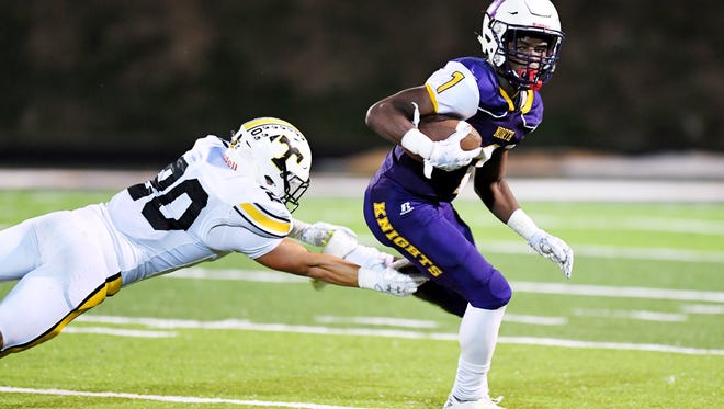 North Henderson's Darren Lammons carries the ball as Tuscola's Nick Cole reaches for his leg Sept. 15 in Hendersonville.