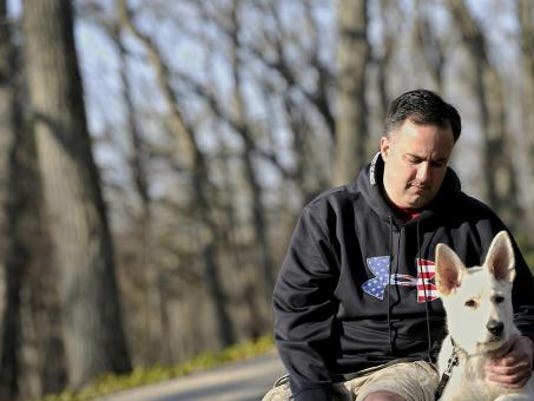 Lance Ranck poses with Schotzi, his 14-week-old dog he brought home in January. Ranck's two other dogs, Zoe and Izzy, were killed after they got out of their electric fence and ran into a nearby sheep farm where they were shot. (DAILY RECORD/SUNDAY NEWS--JASON PLOTKIN)