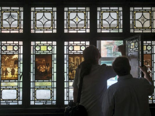 Members of Rudy Collective inspect stained glass windows inside the former Citizens Bank on Continental Square in downtown York on Monday. The windows depict scenes from York in the 1770s.