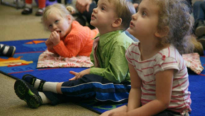 Three-year-old Abraham Hatton, center, sits and listens while children's librarian Gloria Larson reads to a group of pre-school aged children during story time Tuesday, Jan. 12, 2016 at the Washington Branch of the Washington County Library System.