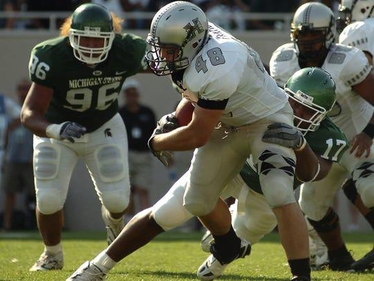Hawaii's B.J. Fruean is tackled by MSU's David Stanton